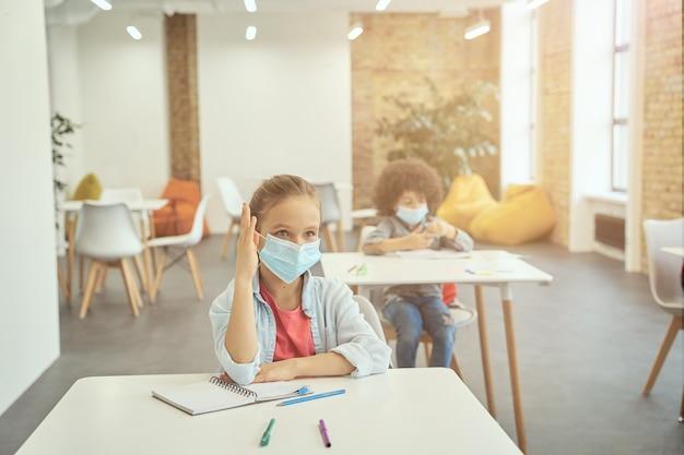 Une petite fille active portant un masque protecteur pendant l'épidémie de coronavirus a levé la main