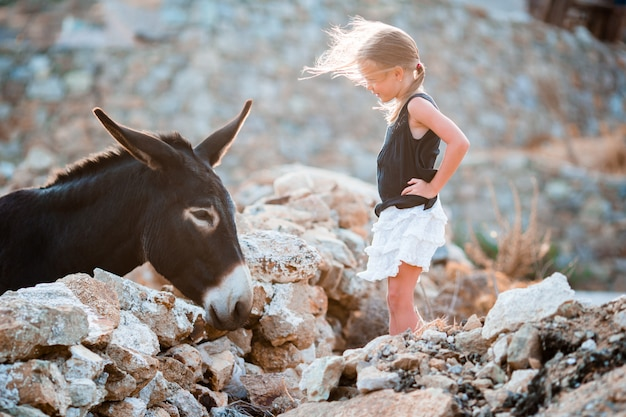 Petite fille adorable avec un âne à mykonos