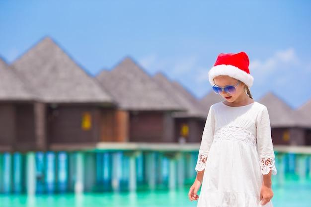 Petite fille adorable au bonnet rouge sur la plage
