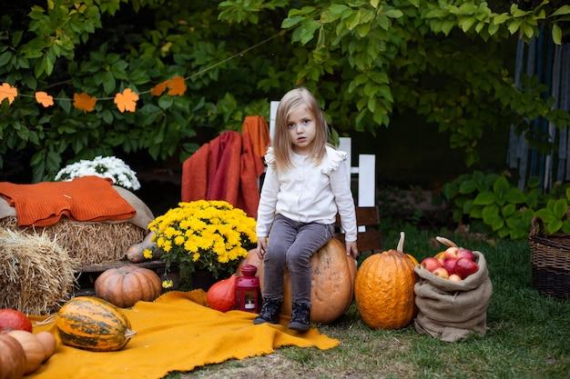 Petite fille adorable avec citrouille en plein air