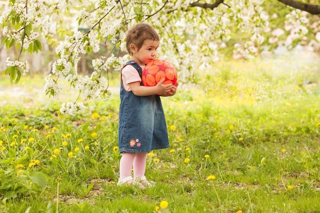 Petite fille adorable dans le jardin, joue avec le ballon