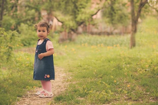 Petite fille adorable dans le jardin, marche sur le chemin