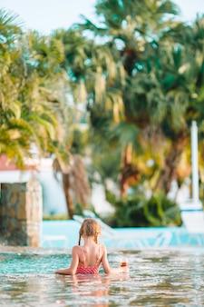 Petite fille adorable dans la piscine extérieure
