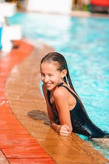 Petite fille adorable dans une piscine extérieure
