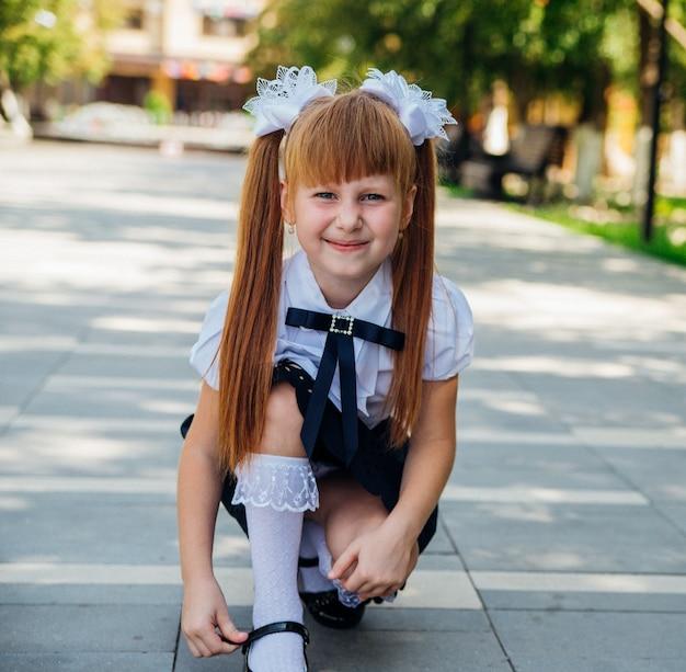 Petite fille adorable drôle dans le parc ou la cour d'école. l'enfant ajuste le fermoir sur la chaussure.