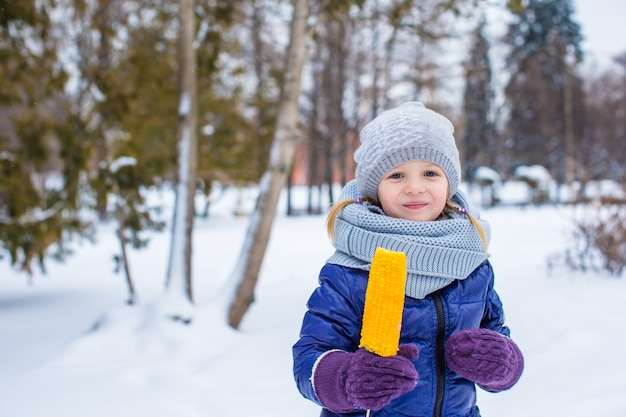 Petite fille adorable avec du maïs savoureux en plein air