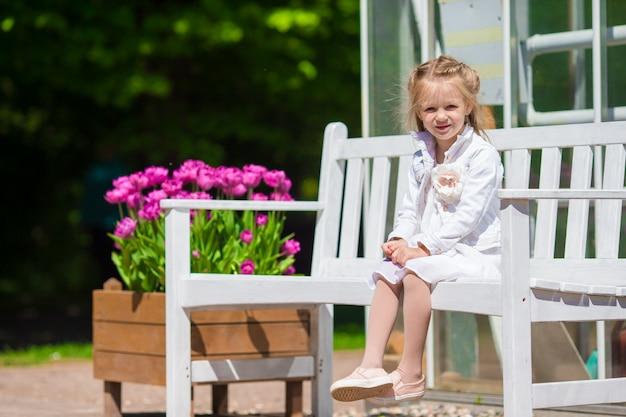 Petite fille adorable avec des fleurs dans le jardin des tulipes