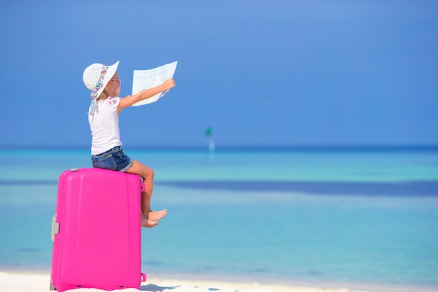 Petite fille adorable avec gros bagages et carte d'île sur la plage blanche