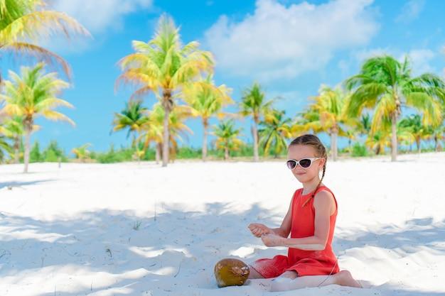 Petite fille adorable avec grosse noix de coco sur la plage