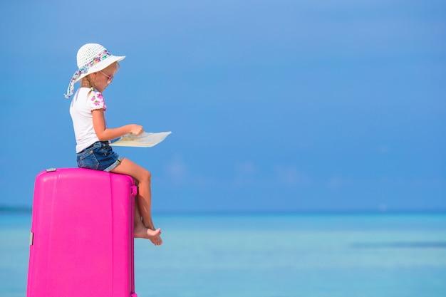 Petite fille adorable avec grosse valise rose et carte sur la plage blanche