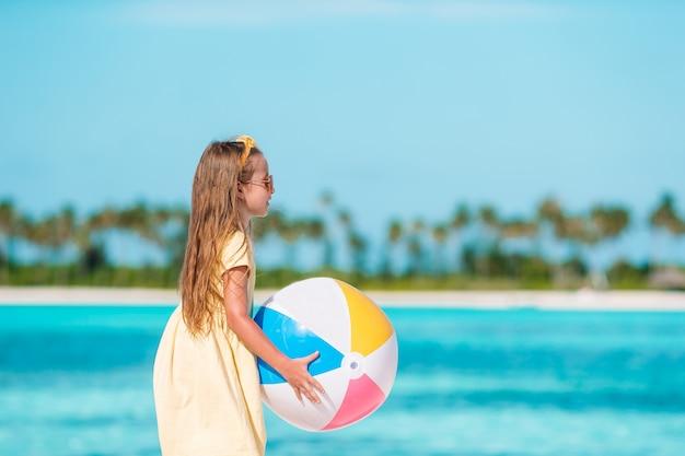 Petite fille adorable jouant sur la plage avec ballon