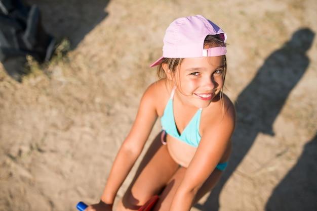 Petite fille adorable jouer sur cheval jouet sur une aire de jeux