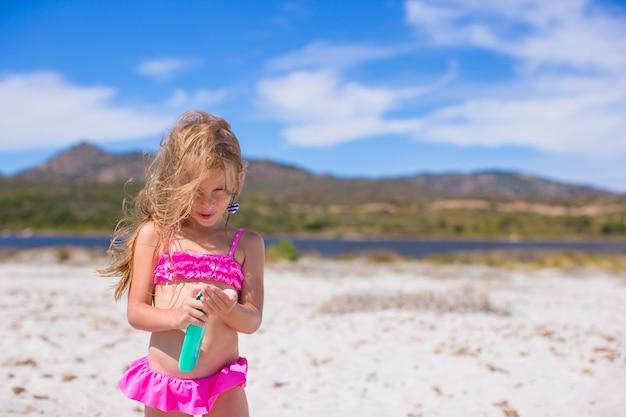 Petite fille adorable en maillot de bain avec une bouteille de lotion de bronzage