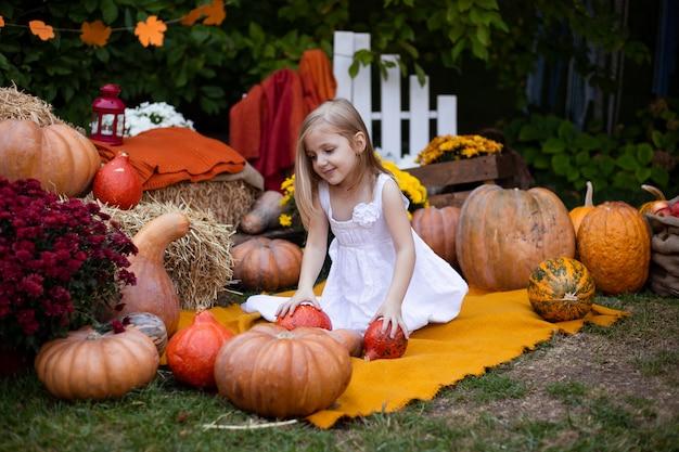 Petite fille adorable mignonne avec citrouille en plein air