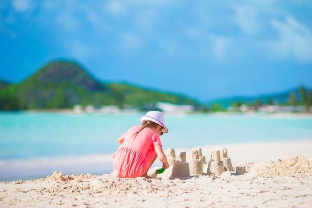 Petite fille adorable à la plage tropicale faisant le château de sable