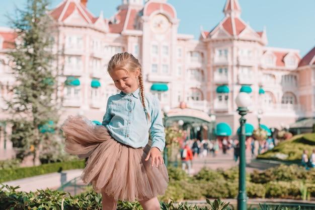 Petite fille adorable en robe de cendrillon au parc disneyland de conte de fées