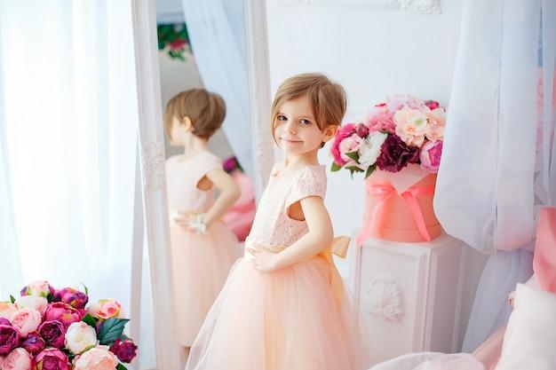 Petite fille adorable en robe posant et en regardant loin dans la chambre remplie de fleurs.