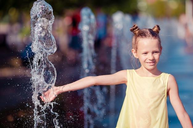 Petite fille adorable s'amuser dans la fontaine de la rue à une journée chaude et ensoleillée