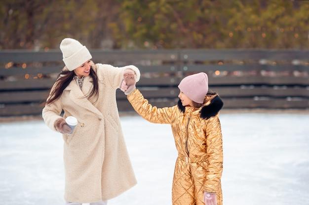 Petite fille adorable avec sa mère patinant sur une patinoire