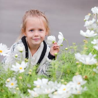 Petite fille adorable, sentant les fleurs colorées à l'extérieur