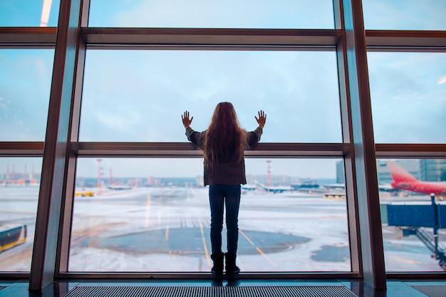 Petite fille à l'aéroport près de la grande fenêtre en attendant l'embarquement
