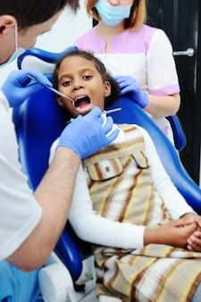 Petite fille africaine à la peau foncée en dentisterie