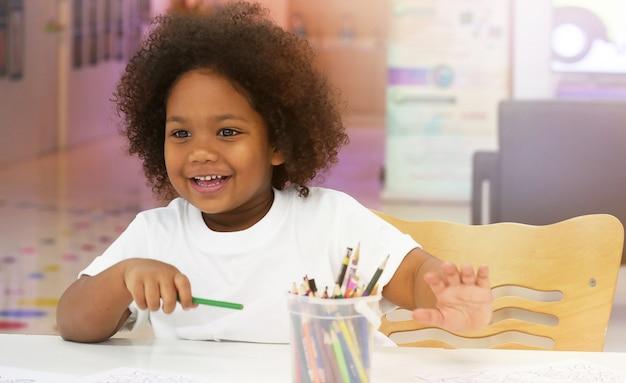 Petite fille africaine souriante en dessinant avec bonheur.