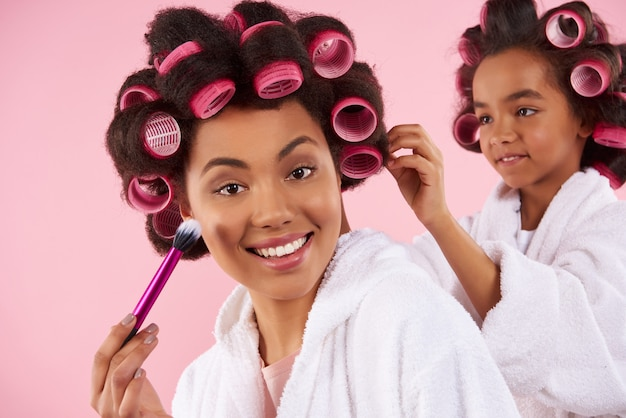 Petite fille afro-américaine en bigoudis fait