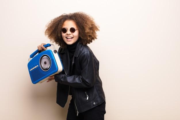 Petite fille afro-américaine contre un mur plat, écouter de la musique avec une radio à l'ancienne