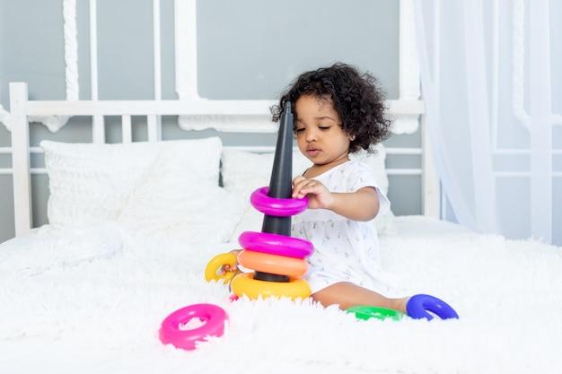 Une petite fille afro-américaine joue et collectionne une pyramide colorée à la maison sur le lit
