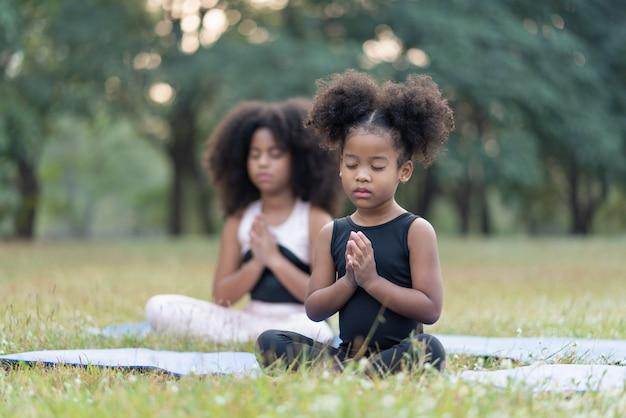 Petite fille afro-américaine souriante et assise sur un tapis roulant, pratique le yoga de méditation dans un parc en plein air