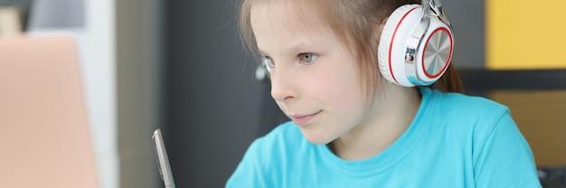 Une petite fille d'âge préscolaire dans des écouteurs s'assoit au bureau pour étudier en ligne sur un ordinateur portable