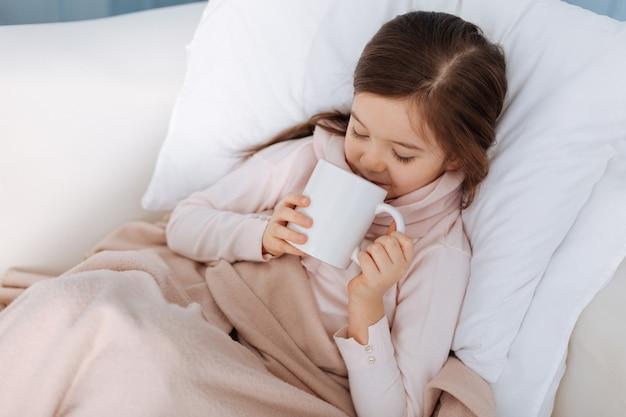 Petite fille agréable au lit et boire du thé tout en souffrant de la grippe