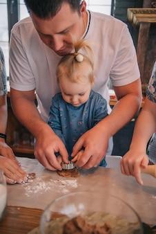 Une petite fille aide un homme à cuisiner des biscuits de noël au gingembre, étale la pâte.