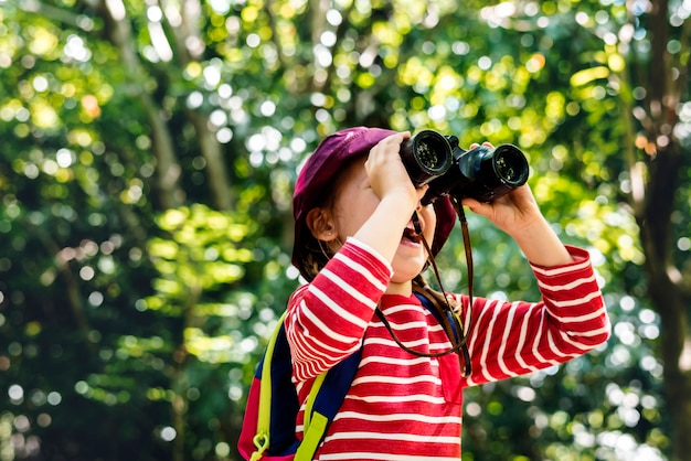 Petite fille à l'aide de jumelles dans la forêt