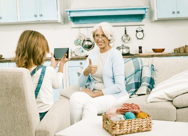 Petite-fille aide sa belle grand-mère avec le vidéoblogging