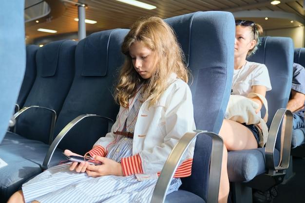 Petite fille à l'aide de smartphone assis à l'intérieur du ferry