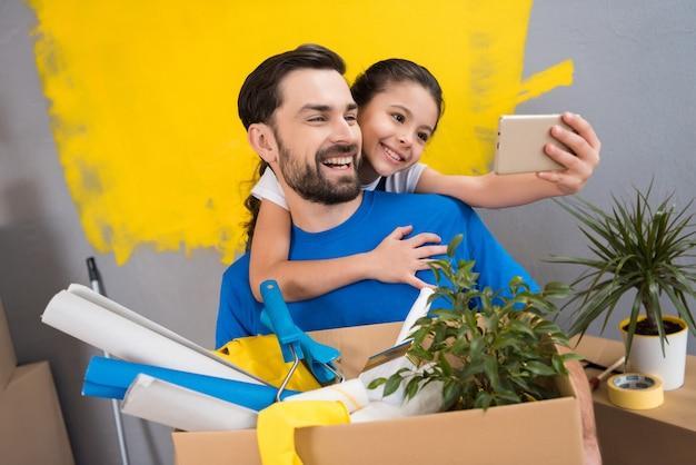 Petite fille à l'aide de smartphone fait selfie avec son père