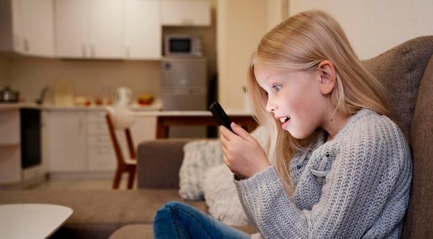 Petite fille à l'aide de smartphone à la maison