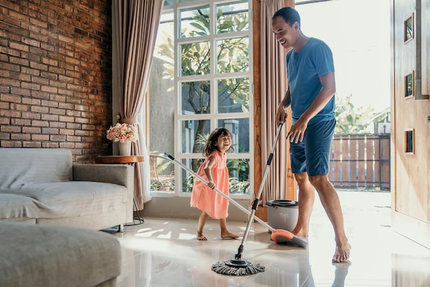 Petite fille aide son papa à faire des corvées
