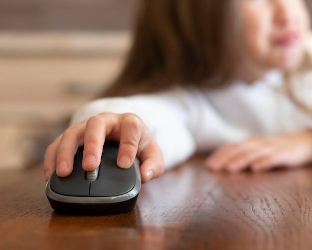 Petite fille à l'aide d'une souris d'ordinateur