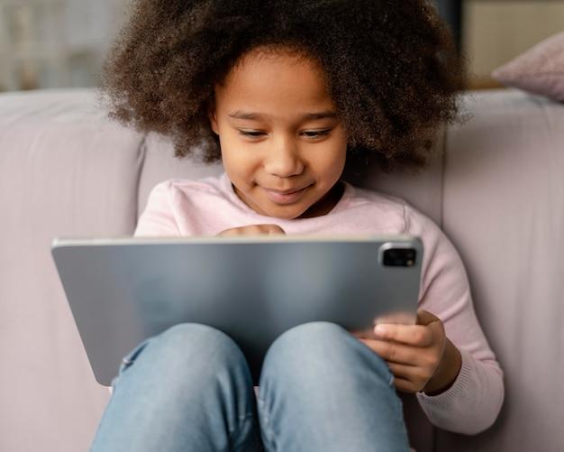 Petite fille à l'aide de tablette à la maison