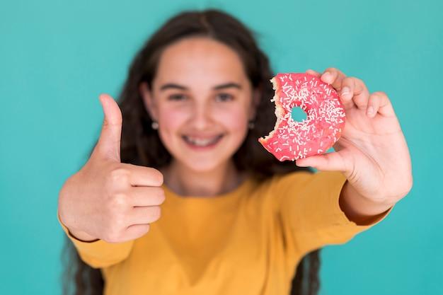 Petite fille aimant un beignet glacé