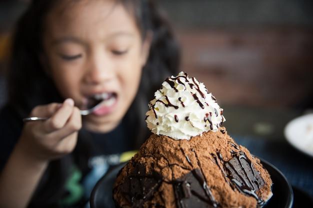 Petite fille aime manger une glace de style coréen ou bingsu avec une saveur de chocolat