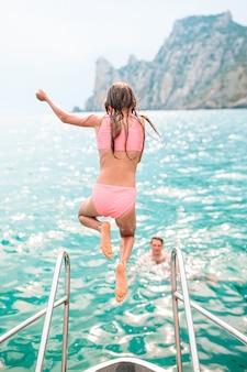 Petite fille aime naviguer sur un bateau en pleine mer. kid nager et éclabousser dans l'eau claire de la baie