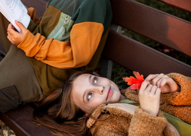 Petite fille allongée sur un banc pendant que son amie lit