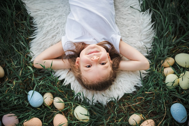 Petite fille allongée entourée d'oeufs de pâques