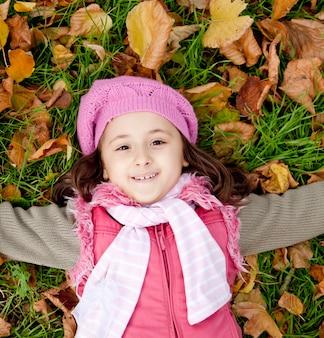 Petite fille allongée sur l'herbe et les feuilles dans le parc. tir en plein air.