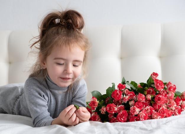 Petite fille allongée sur le lit avec bouquet de roses roses.