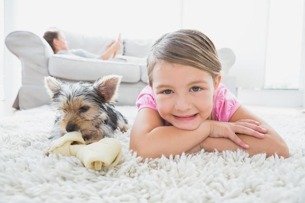 Petite fille allongée sur le tapis avec yorkshire terrier, souriant à la caméra